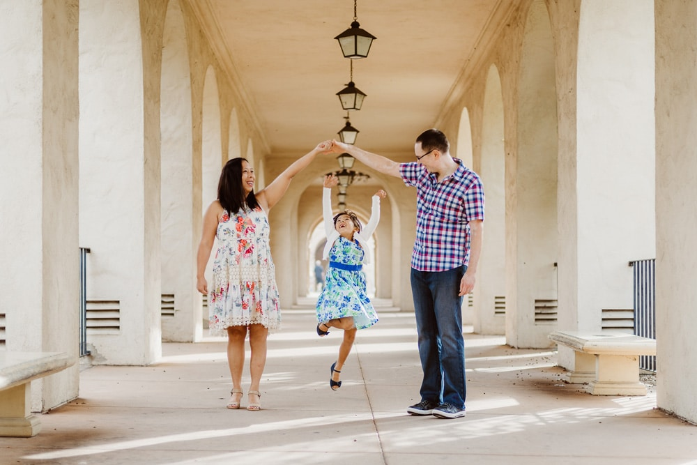 San Diego Family Photography, little girl jumping to touch her parents' hands