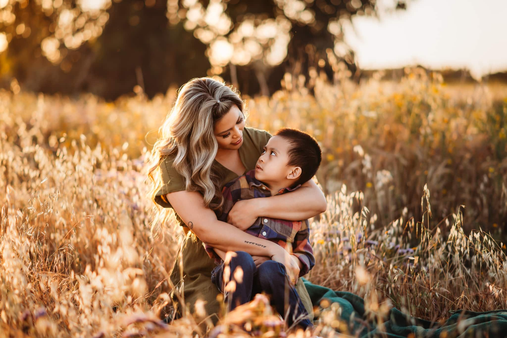 Mother and 5 year old son embraced together at Fiesta Island in a golden field