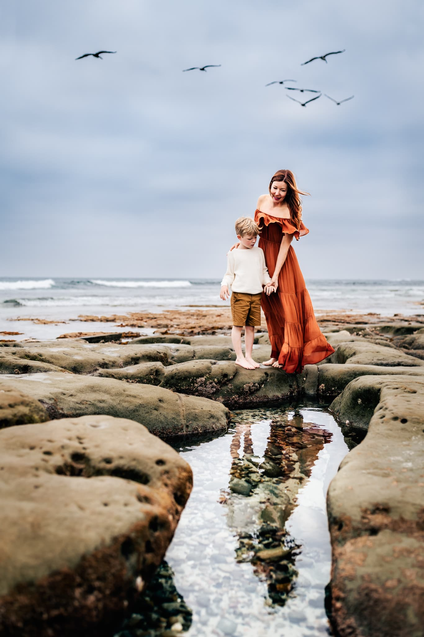 Mother and young son standing at Windansea Beach in San Diego overlooking the tidepools