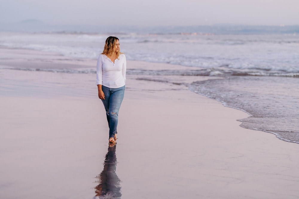 Individual Portrait Photography, woman walking in the sand next to water