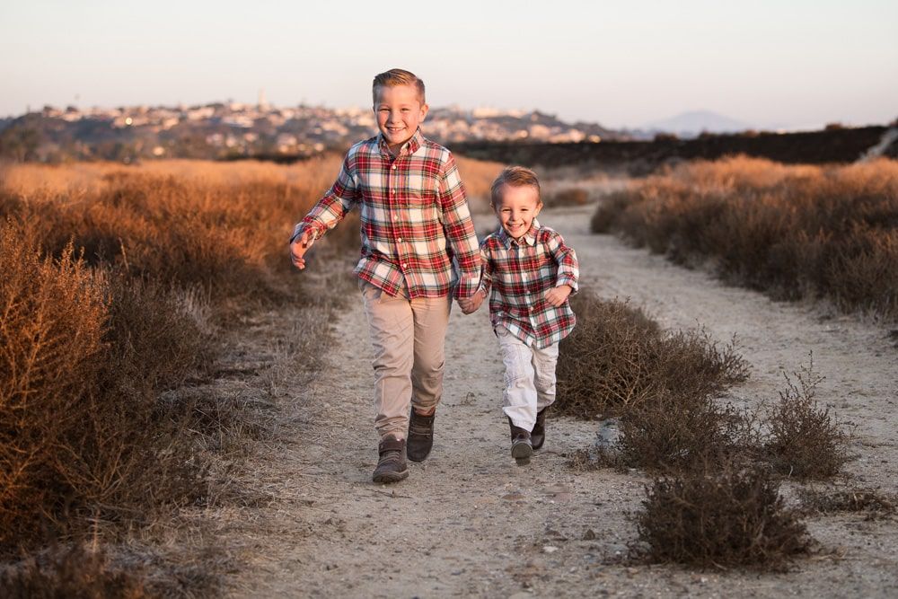 San Diego Children Photography, brothers running on dirt path with matching red plaid shirts