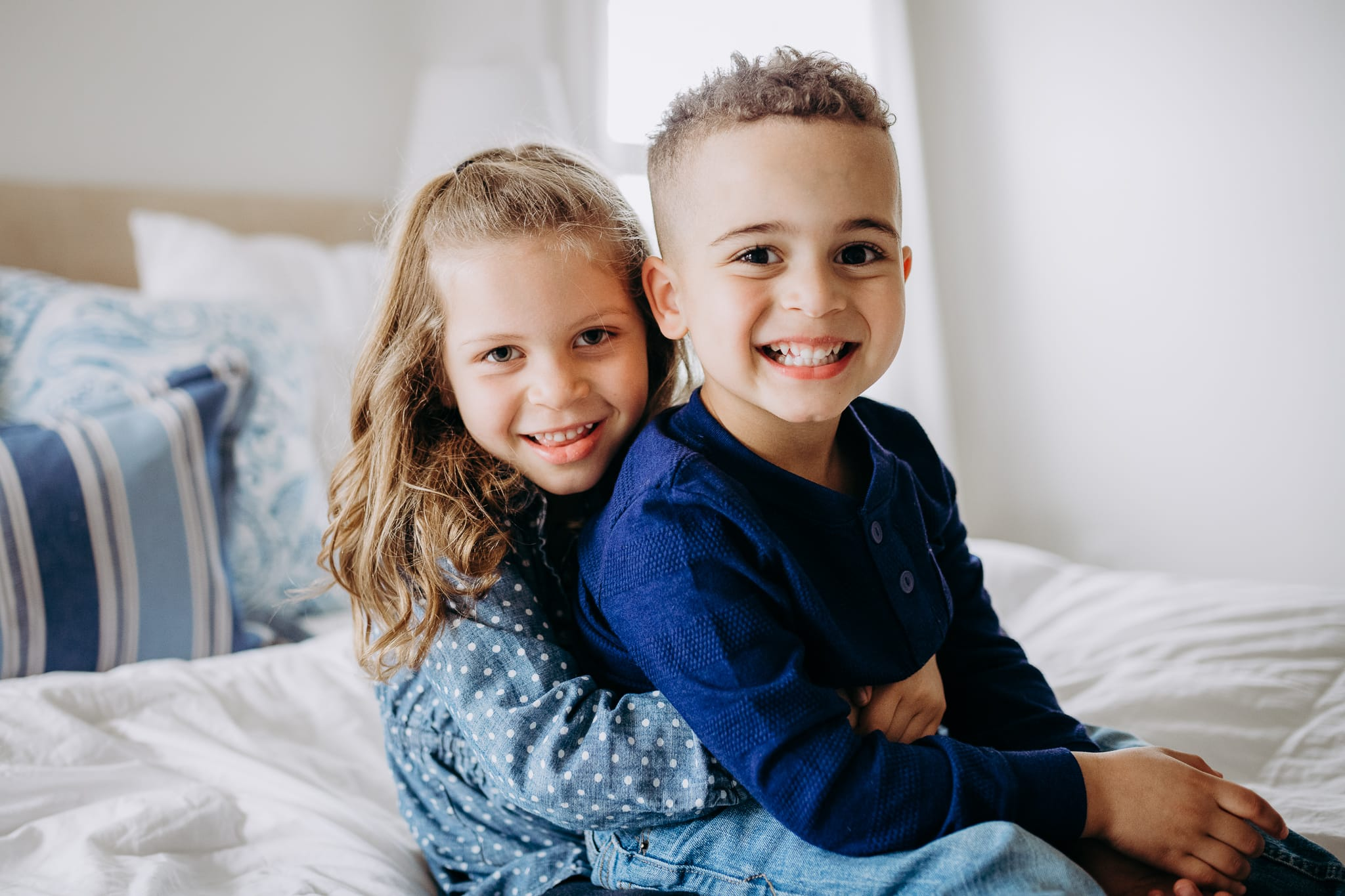 San Diego Children Photography, Brother and Sister sitting on white bed