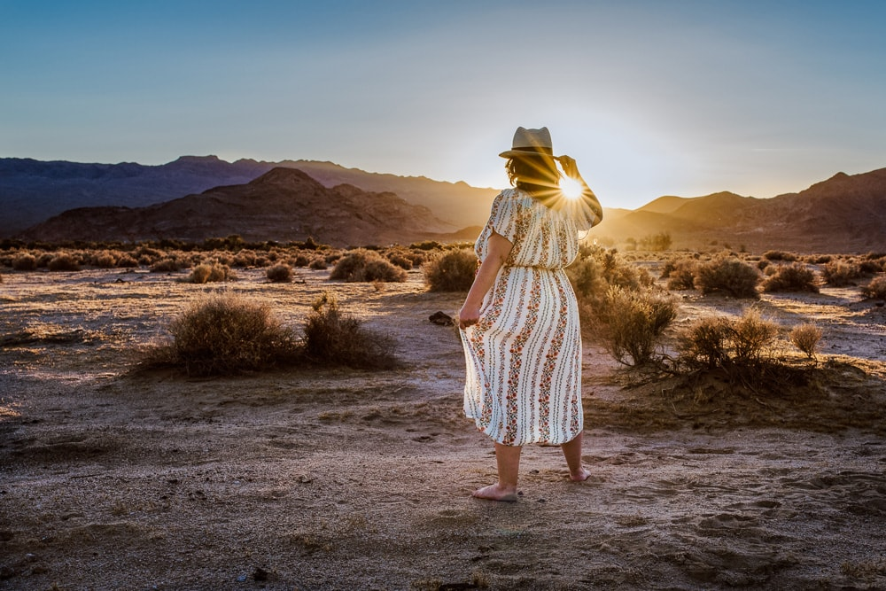 Individual Portrait Photography, woman standing in the desert looking toward the setting sun