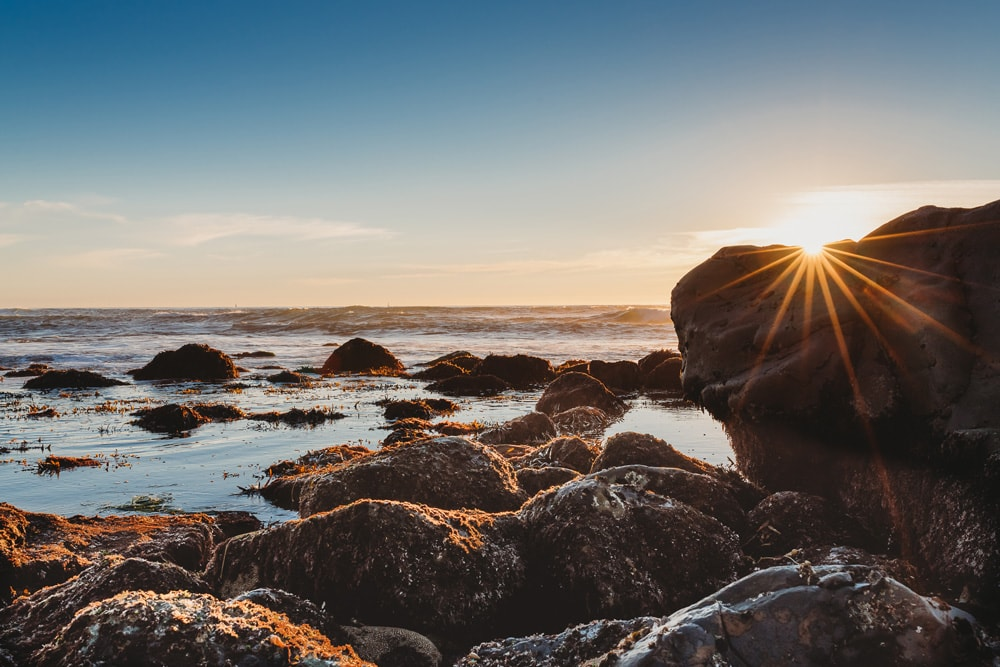 Landscape and Macro Photography,  sun poking over the rocks at the beach