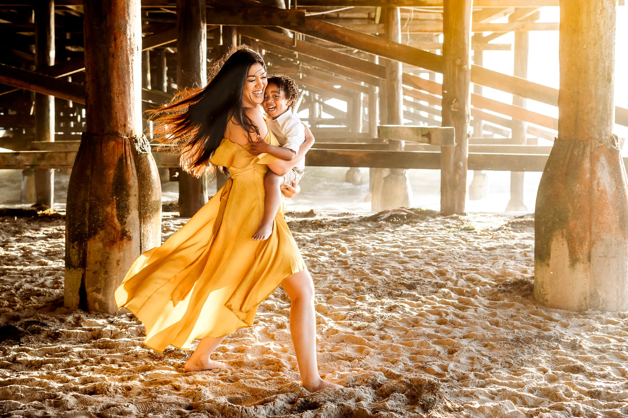 San Diego Family Photography, Mother and young child walking beneath pier by the ocean