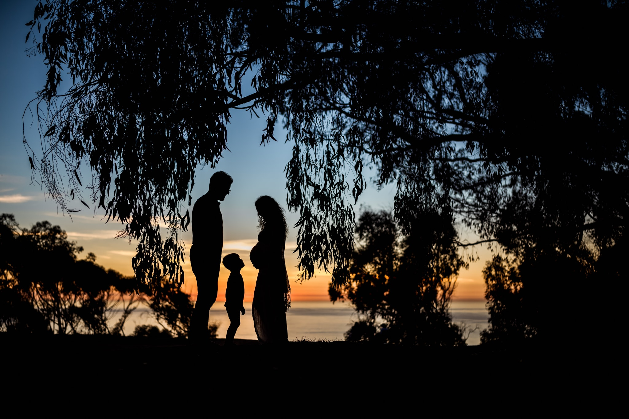 Pregnant mother and her husband and son in silhouette at sunset in La Jolla