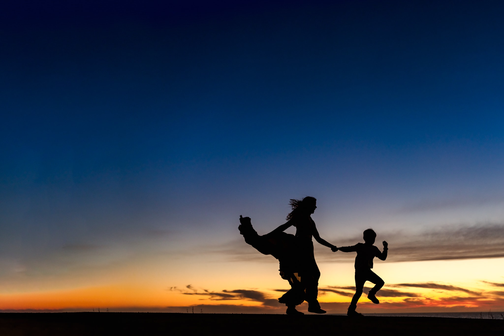 Mother and son silhouettes against sunset sky at Sunset Cliffs, San Diego